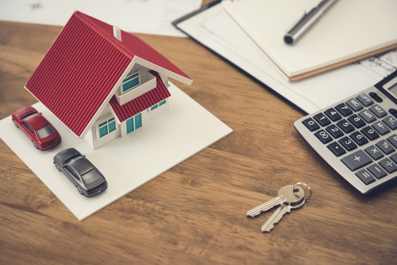 House model, key and calculator with documents on the table - real estate and property concept