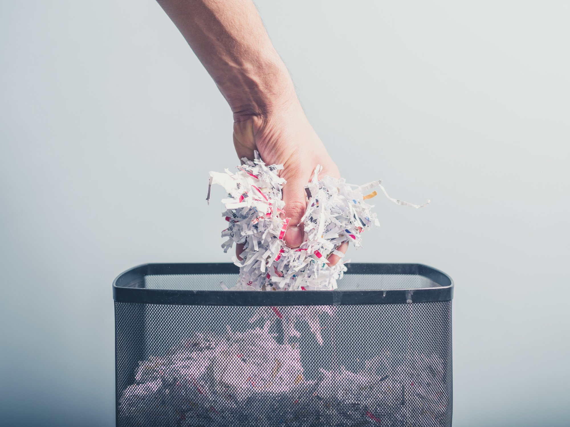 A hand is putting a bunch of shredded paper in a waste paper basket